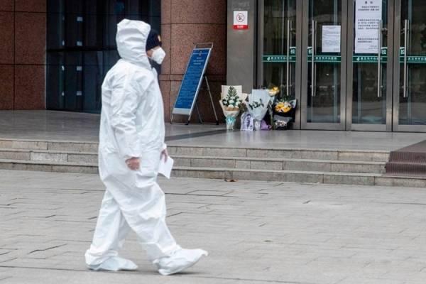 Một nhân viên y tế đi qua nơi đặt hoa tưởng niệm bác sĩ Lý Văn Lượng ở Vũ Hánngày 7/2. .